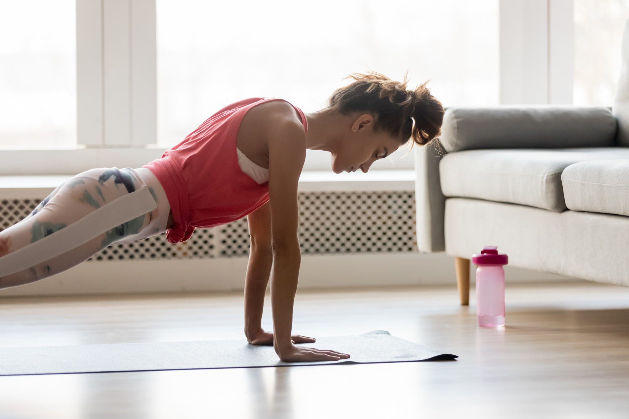 Sportive girl doing push press ups exercise at home