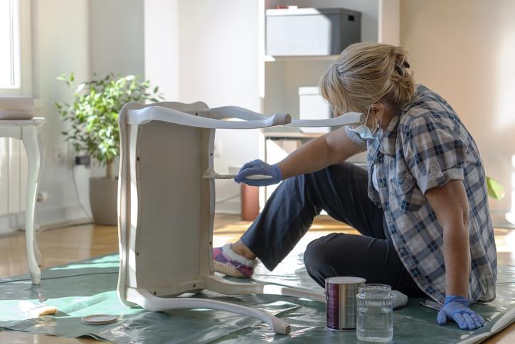 Senior woman painting furniture